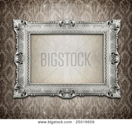 Ornamental silver frame on an aged damask wallpaper