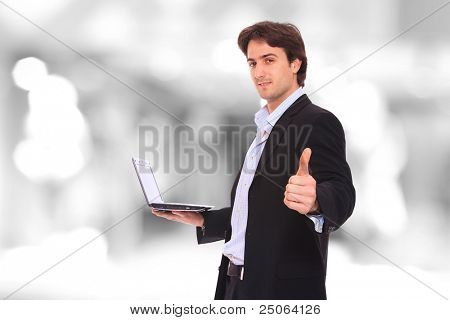 Closeup of a young smiling business man standing holding his computer thumb up  in a light and mordern business environement