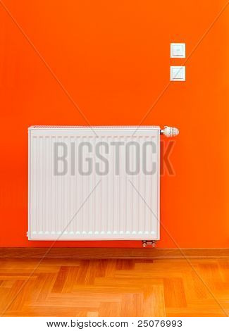 Radiator heater attached on the orange wall