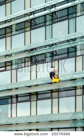 Window washer hanging outside facade