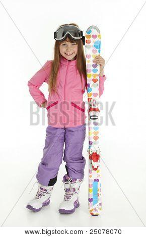 Full length photo of little girl dressed in ski wear holding skis, standing on white background.