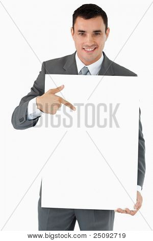 Smiling businessman pointing at the sign in his hands against a white background