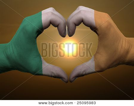 Heart And Love Gesture By Hands Colored In Ireland Flag During Beautiful Sunrise