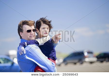 Father Holding Disabled Son On The Beach