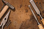 Flat Lay With Old Shabby Mechanical Tools On Brown Surface poster
