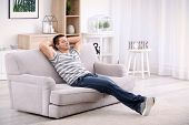 Young man relaxing on sofa at home poster