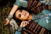 Beautiful hippie girl lying in a grass. Modern boho style. Beauty, fashion,  poster