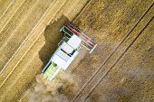 Aerial View Of Harvester Combine Working On Field poster