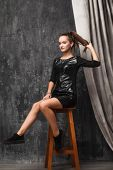 Beautiful Young Girl Sitting On A High Wooden Bar Stool, In The Studio, Hair In The Tail, Holding A  poster