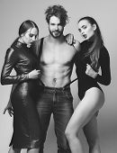 Man And Pretty Girls With Seductive Faces On Grey Background. Women In Sexy Bodysuits Hug Bearded Ma poster