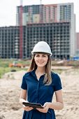 Female Construction Engineer. Architect With A Tablet Computer At A Construction Site. Young Woman L poster