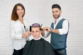 Постер, плакат: Female And Male Hairstylists Doing Haircut For Young Client With Toned Hair Using Plastic Combs For