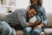 Young Pakistani Man With Pregnant Wife On Sofa. Gray Sofa. Arabian Family Concept. Young Mother And  poster