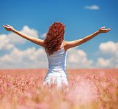 Happy woman enjoying the life in the field with flowers. Nature beauty, blue cloudy sky and colorful poster
