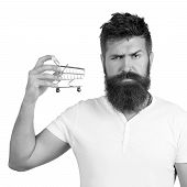 E-commerce And Shopping Concept. Bearded Man Wearing White T-shirt Holding Mini Shopping Cart On Rig poster