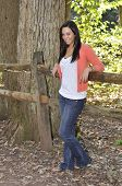 image of split rail fence  - teenage girl outdoors at park in autumn leaning on a split rail fence by a tree - JPG