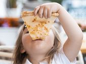 A Young Girl With Plaits Is Eating A Piece Of Pizza poster