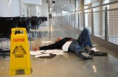 stock photo of skid  - Man lies on the wet floor on which he slipped in spite of caution sign selective focus on man - JPG