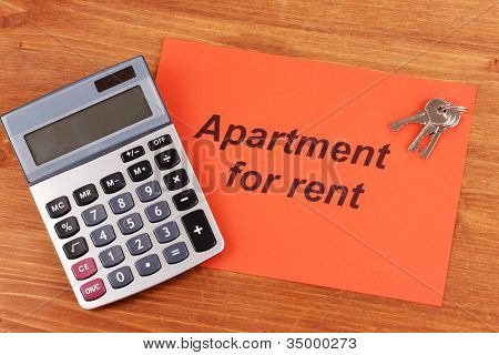 Advertise rental apartmennt on red paper on wooden background close-up