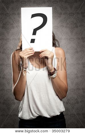 young woman holding interrogation symbol  in front of his face