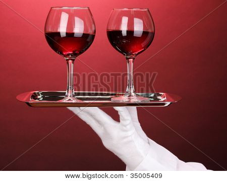 Hand in glove holding silver tray with wineglasses on red background