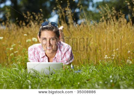Happy attractive female work on her laptop, summer outdoor shoot