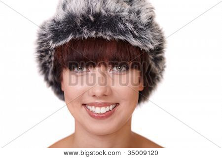 Smiling attractive female in fur hat isolated on white background