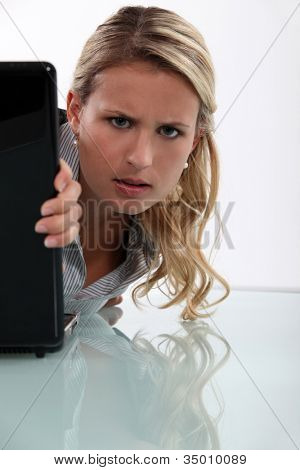 Annoyed woman peeking round her laptop