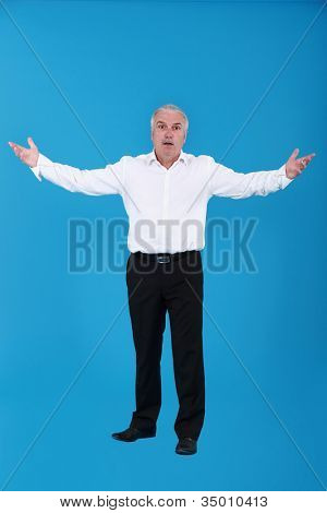 Exasperated man standing with his arms wide open