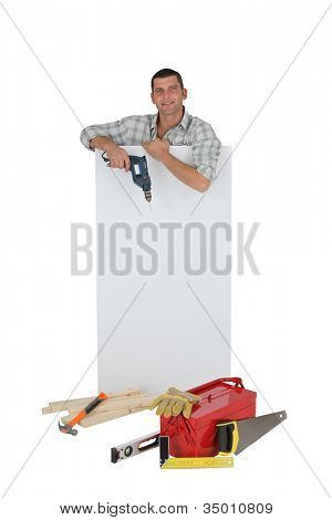 Handyman posing with a blank sign and his tools