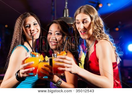 Group of party people - three female girl friends - with cocktails in a bar or club having fun