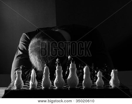 Teenage Boy Slumped Over The Chess Board