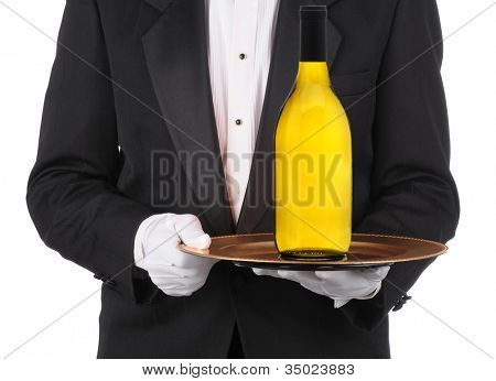 Butler wearing a tuxedo holding a bottle of Chardonnay Wine on a serving tray. Horizontal format showing persons torso only.