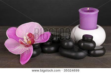 Spa stones with orchid flower and candle on wooden table on grey background
