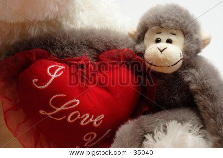 Stuffed Monkey Arms Around Bear Heart