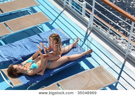 Top view of mother and little daughter lying at deck-chair on ship and playing by hands