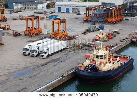 White lorries and orange loaders stand in port. Ship is close to quay.