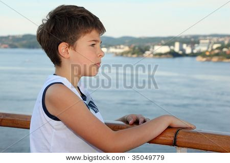 Thoughtful boy stands on board of ship and looks at beautiful landscape