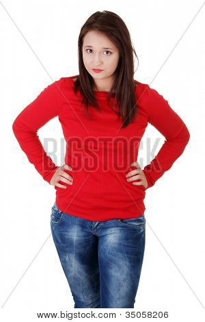 Upset young woman is standing with hands on her hips. Serious girl in red blouse and jeans. Isolated on white background.