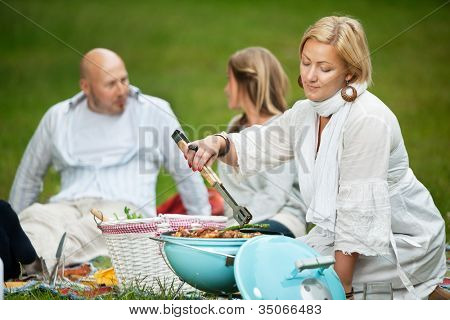 Woman cooking food on a portable barbecue while man and girl sit in background