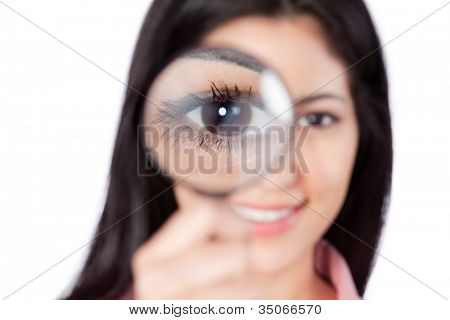 Happy young woman looking through magnifying glass isolated on white background.
