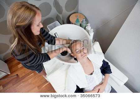 High angle view of relaxed young woman getting a hair wash before haircut at beauty salon