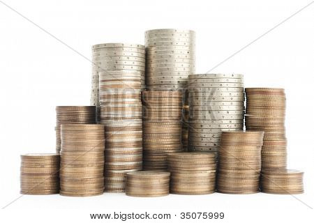 Gold, bronze and silver coins stand vertically in columns, isolated on white. Symmetrically posed coins symbolize wealth, income and profit. Close up shot. There is a hill of coins in columns