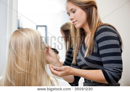 Pretty female artist applying make up to woman in parlor
