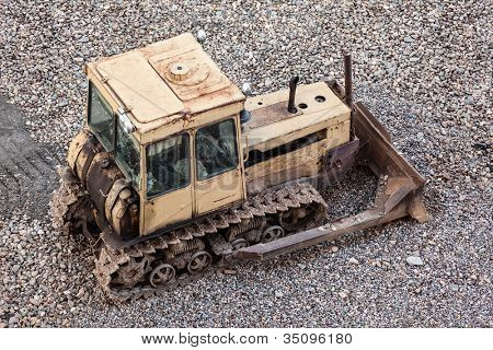 Old rusty earth digging caterpillar bulldozer machine working at building construction site