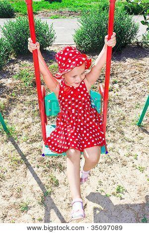A Little Girl Swinging On A Swing