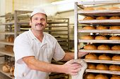 stock photo of pretzels  - baker standing in his bakery in the morning and is baking bread or buns - JPG