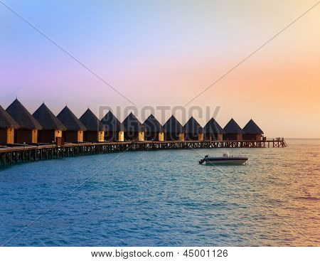 Island in ocean overwater villas at the time sunset.