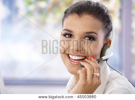 Portrait of pretty young dispatcher, smiling, looking at camera.