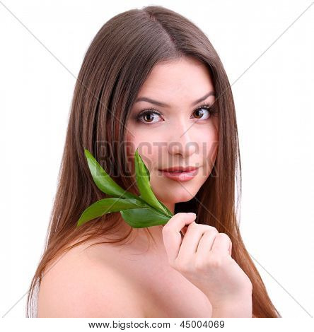 Beautiful young woman with green leafs isolated on white